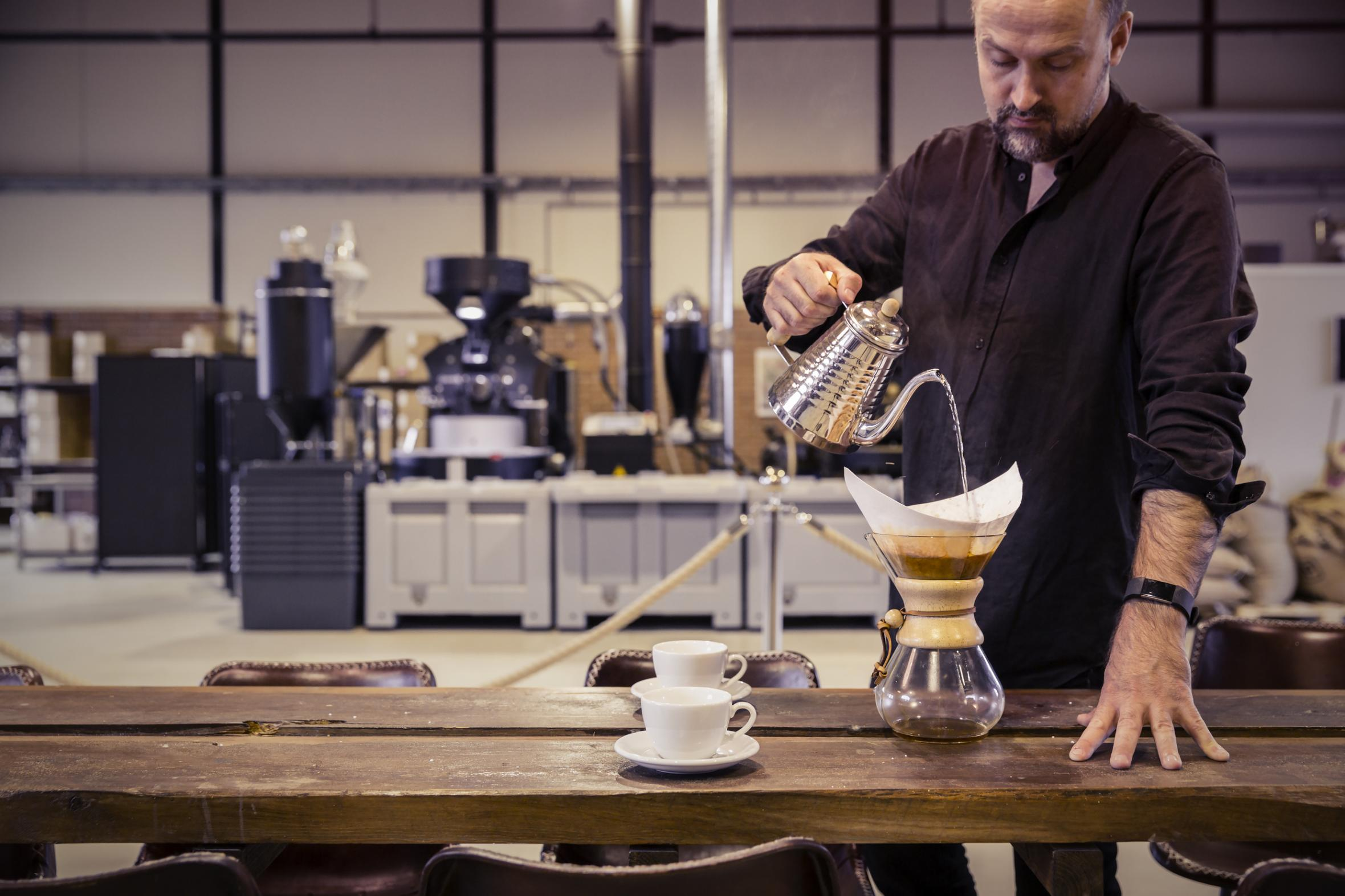 Man pouring coffee in decanter on wooden table