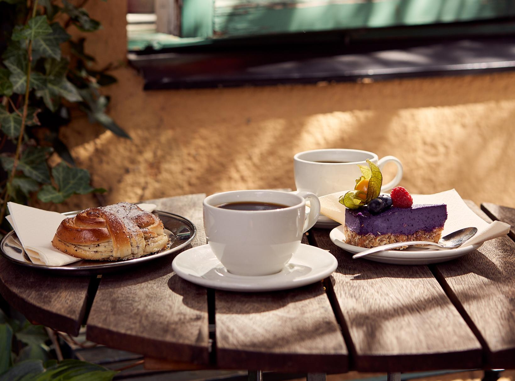 Coffee cup and cakes on outdoor café table