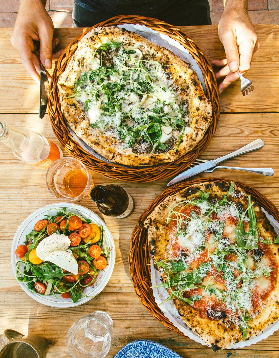 Two pizzas and salad on wooden table