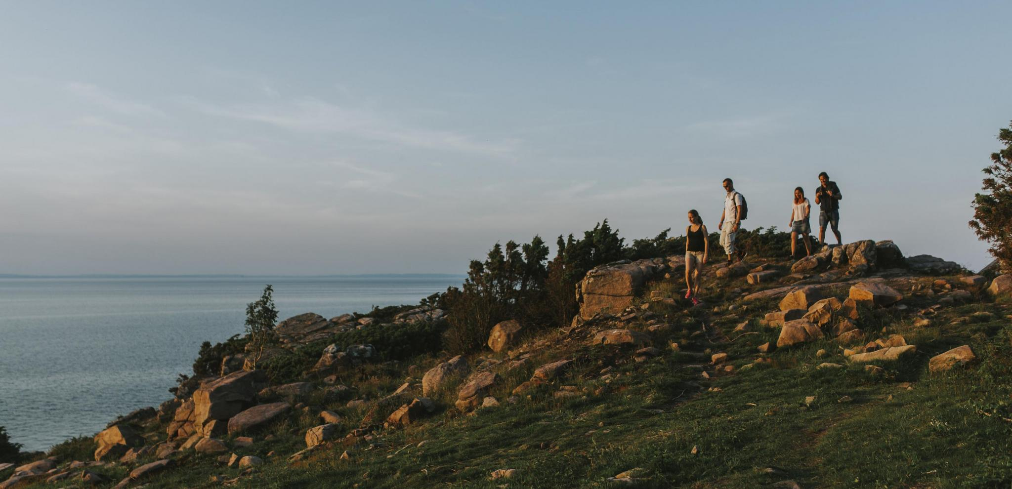 People hiking in sunset over cliffs © Mickael Tannus