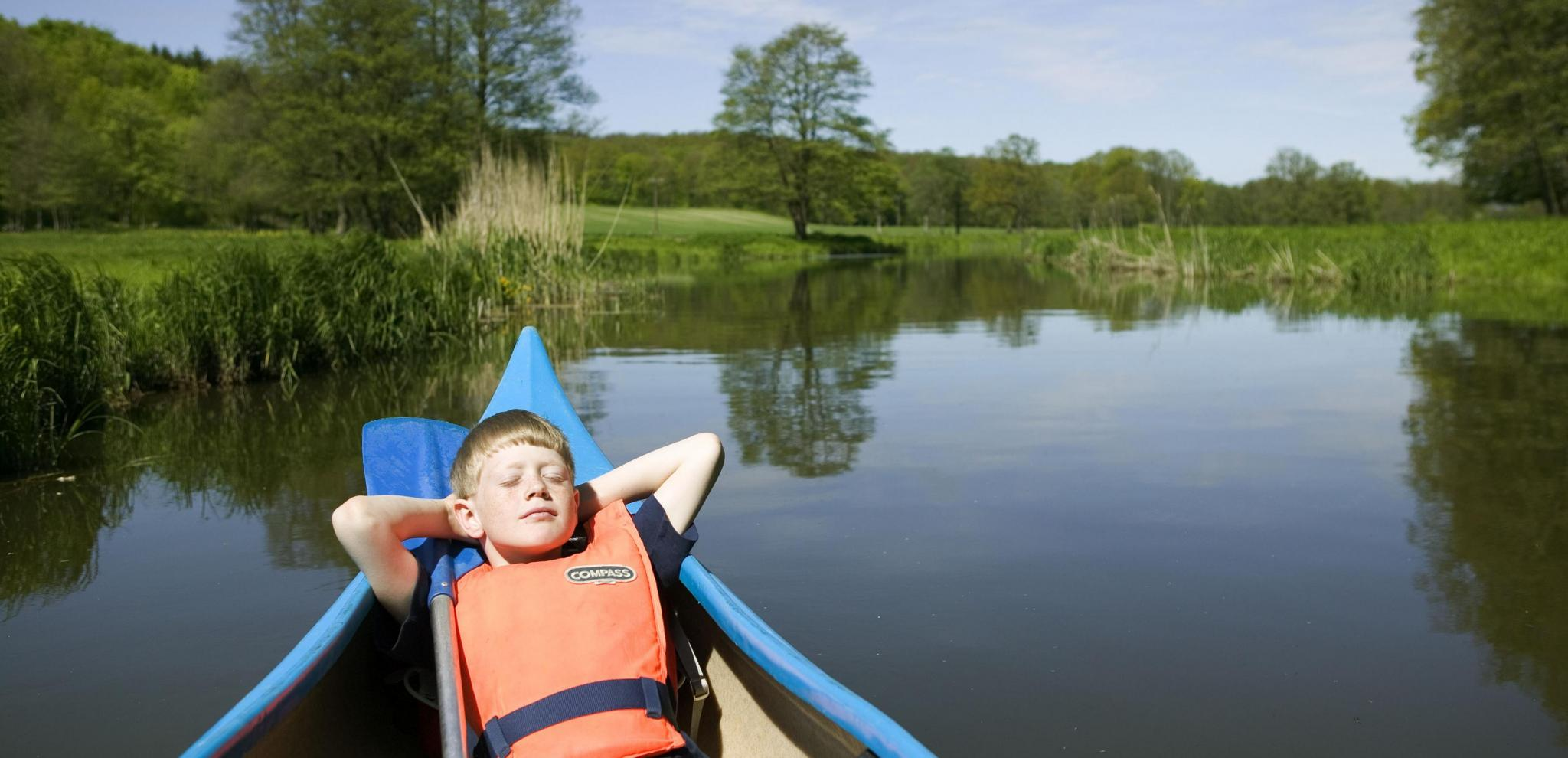 Boy relaxing in a canoe © Sven Persson