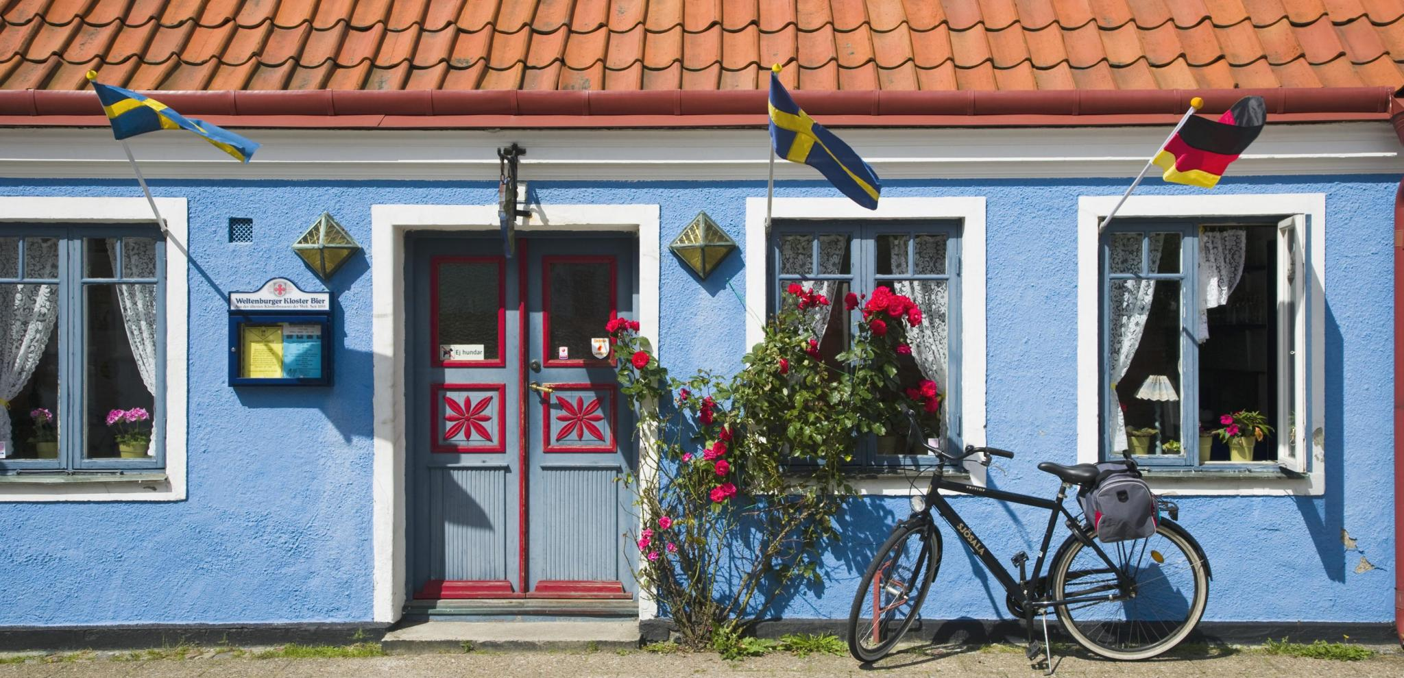 Bicycle parked outside a blue hose in Ystad