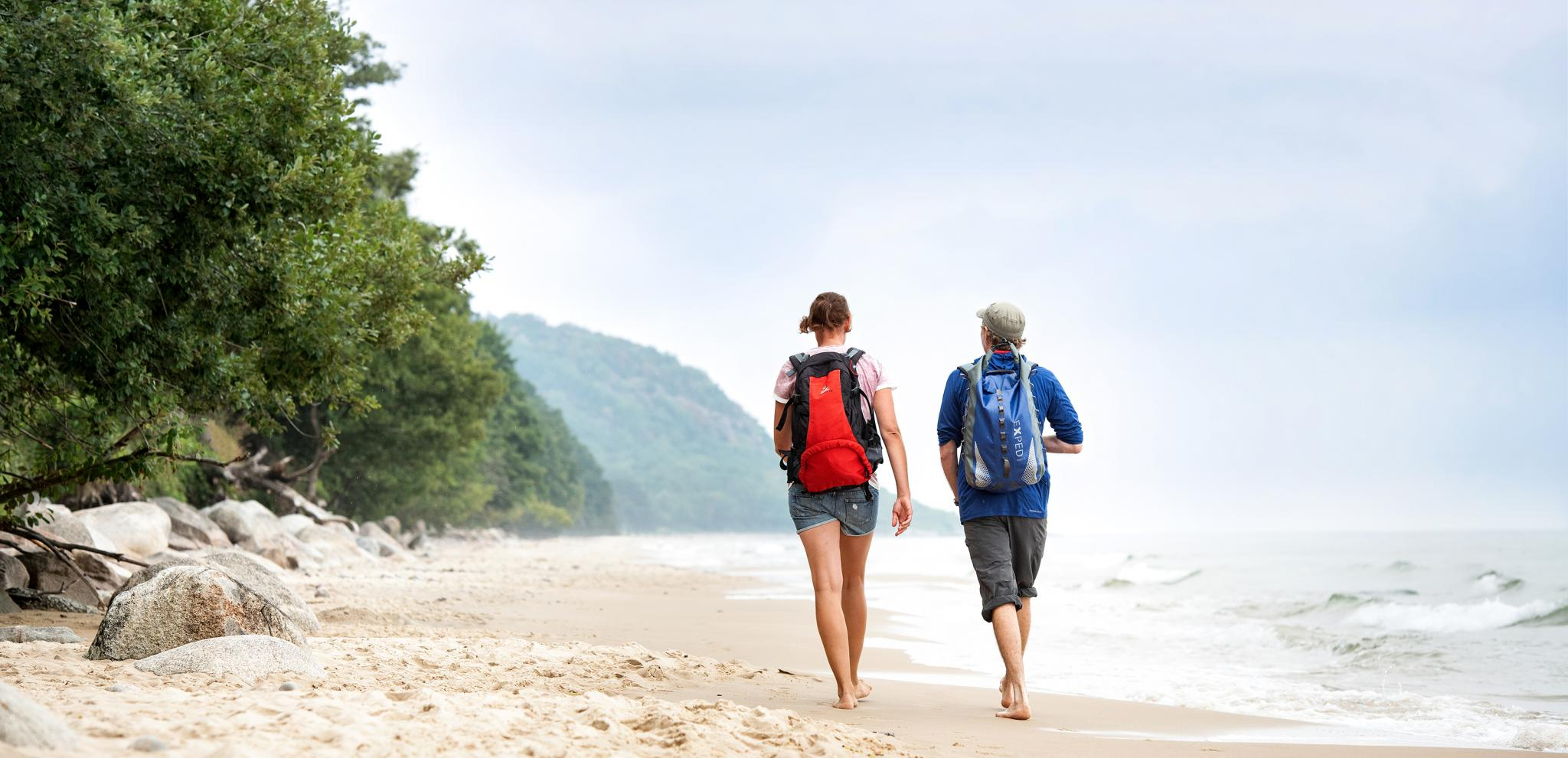 Couple hiking at the beach by Stenshuvud