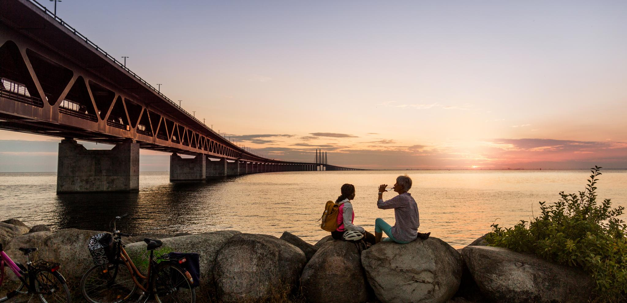 Two people taking a break at sunset next to bridge overlooking sea