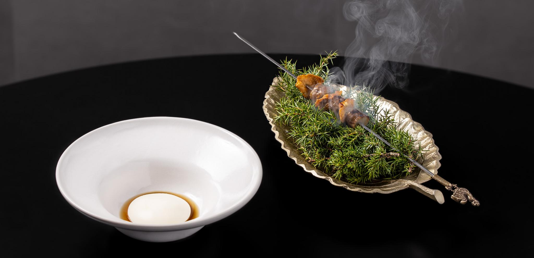 Warm food dish with white plate on black table