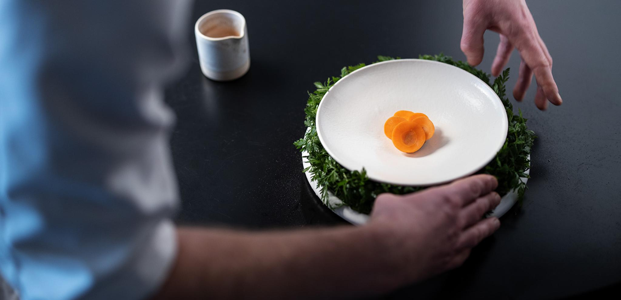 Chef hands around food dish on black table