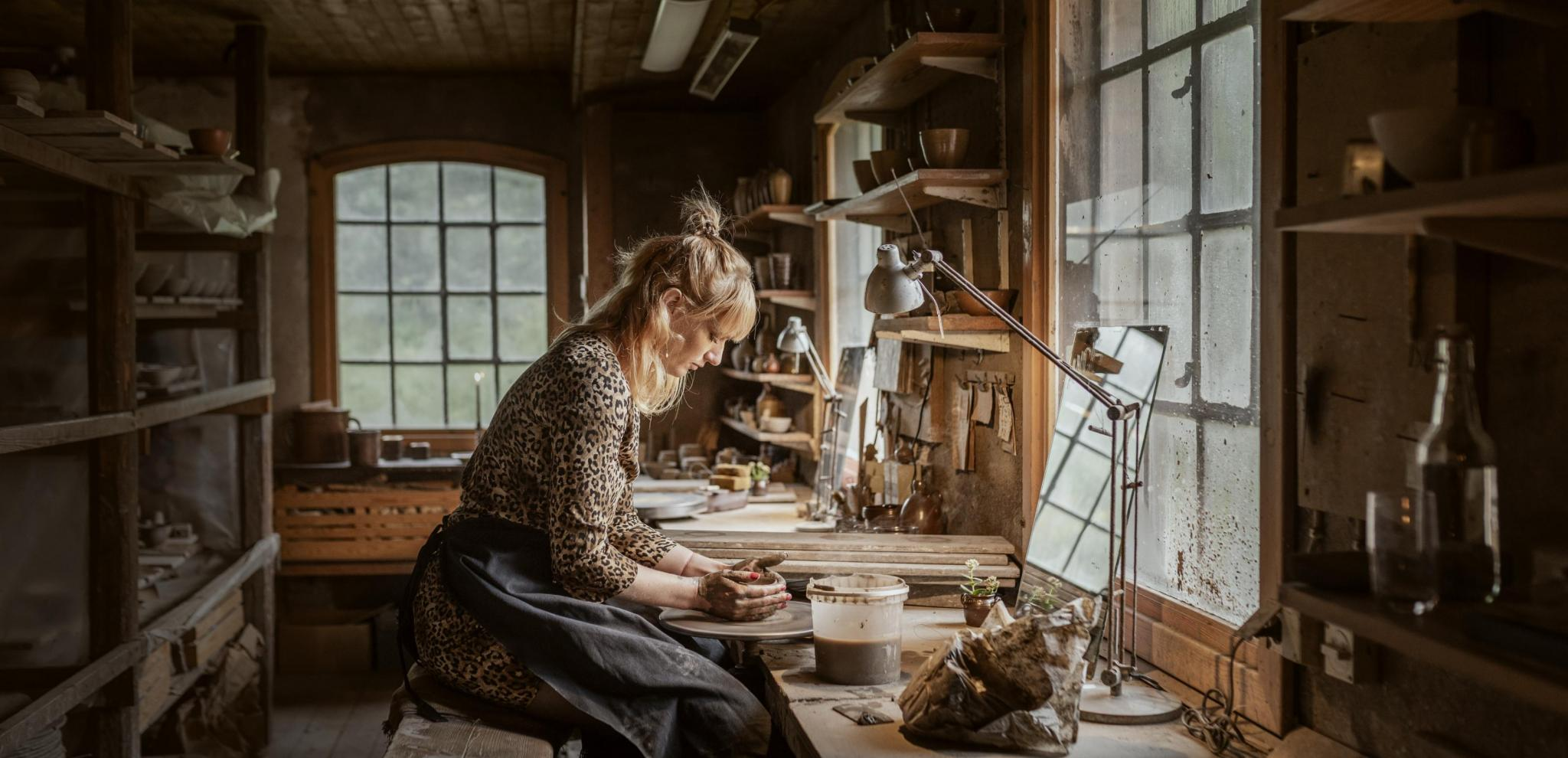 A woman sits on a chair and do pottery