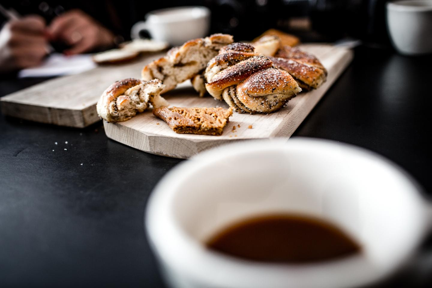 Danish pastries on wooden plank with cup of coffee