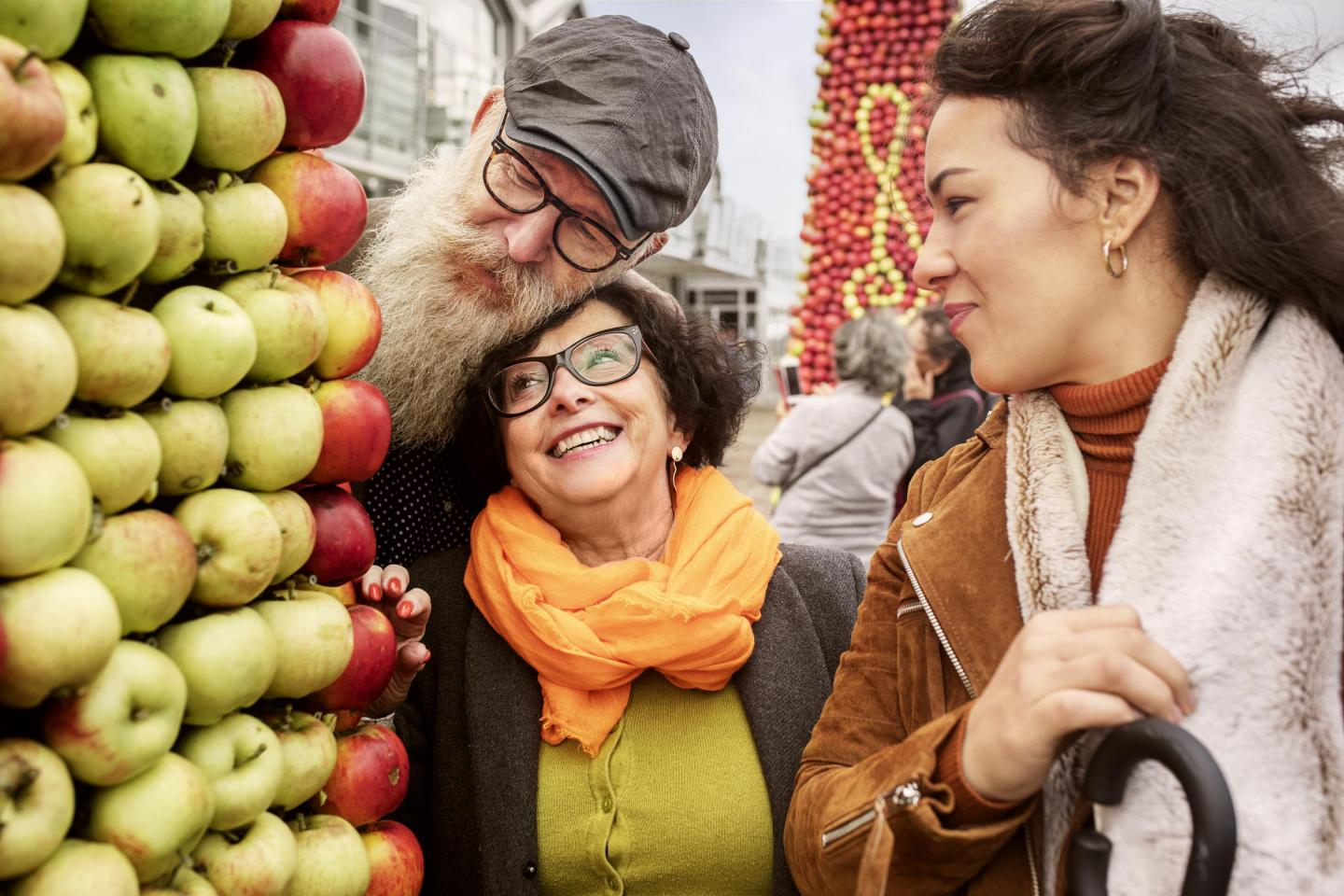 Three happy people at an apple market