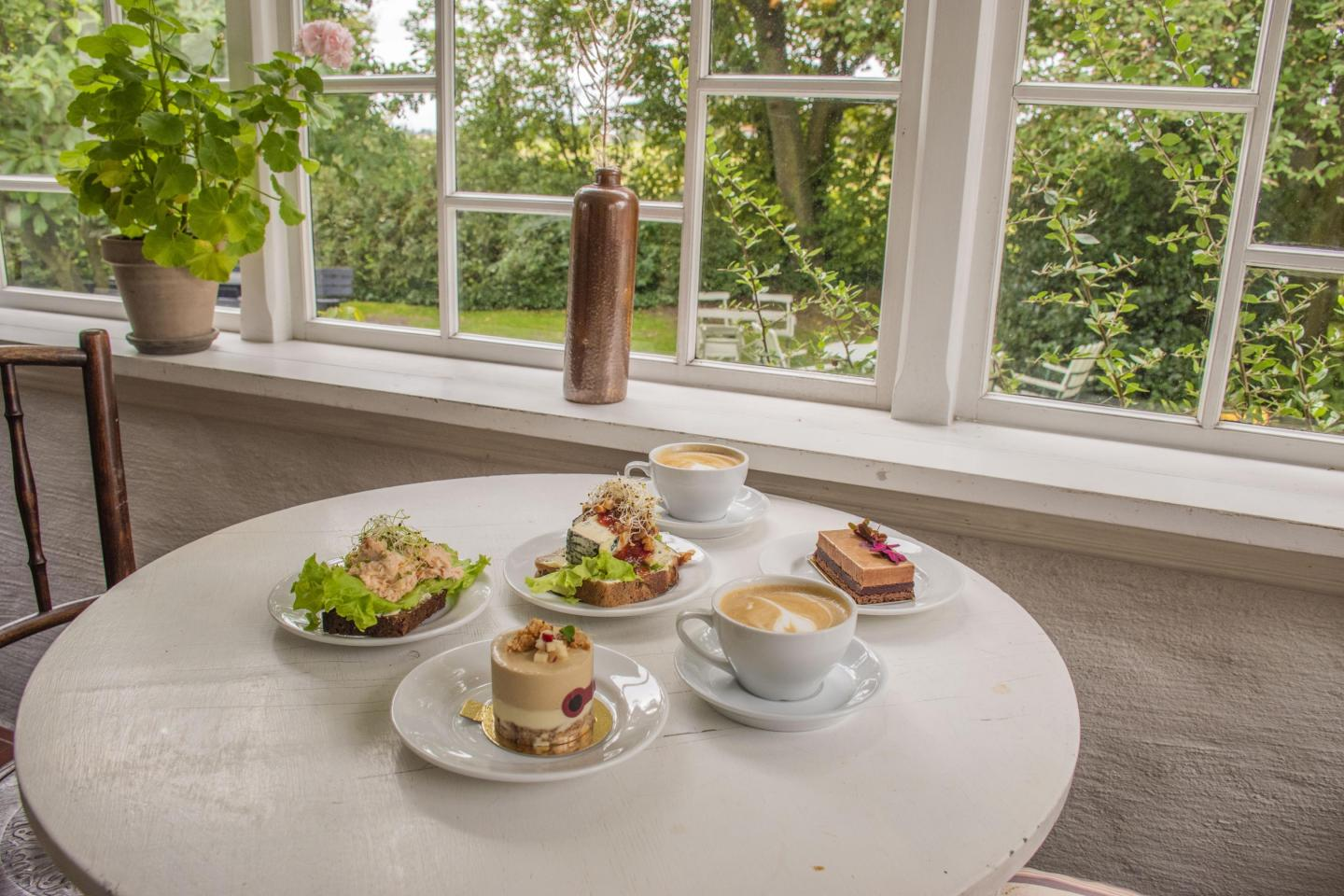 Sandwiches, pastries and coffee placed a round  with a view of a green and lush garden