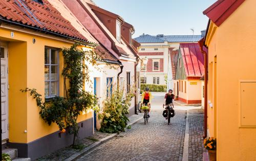 Two cyclists come cycling on a cobbled street among picturesque houses.