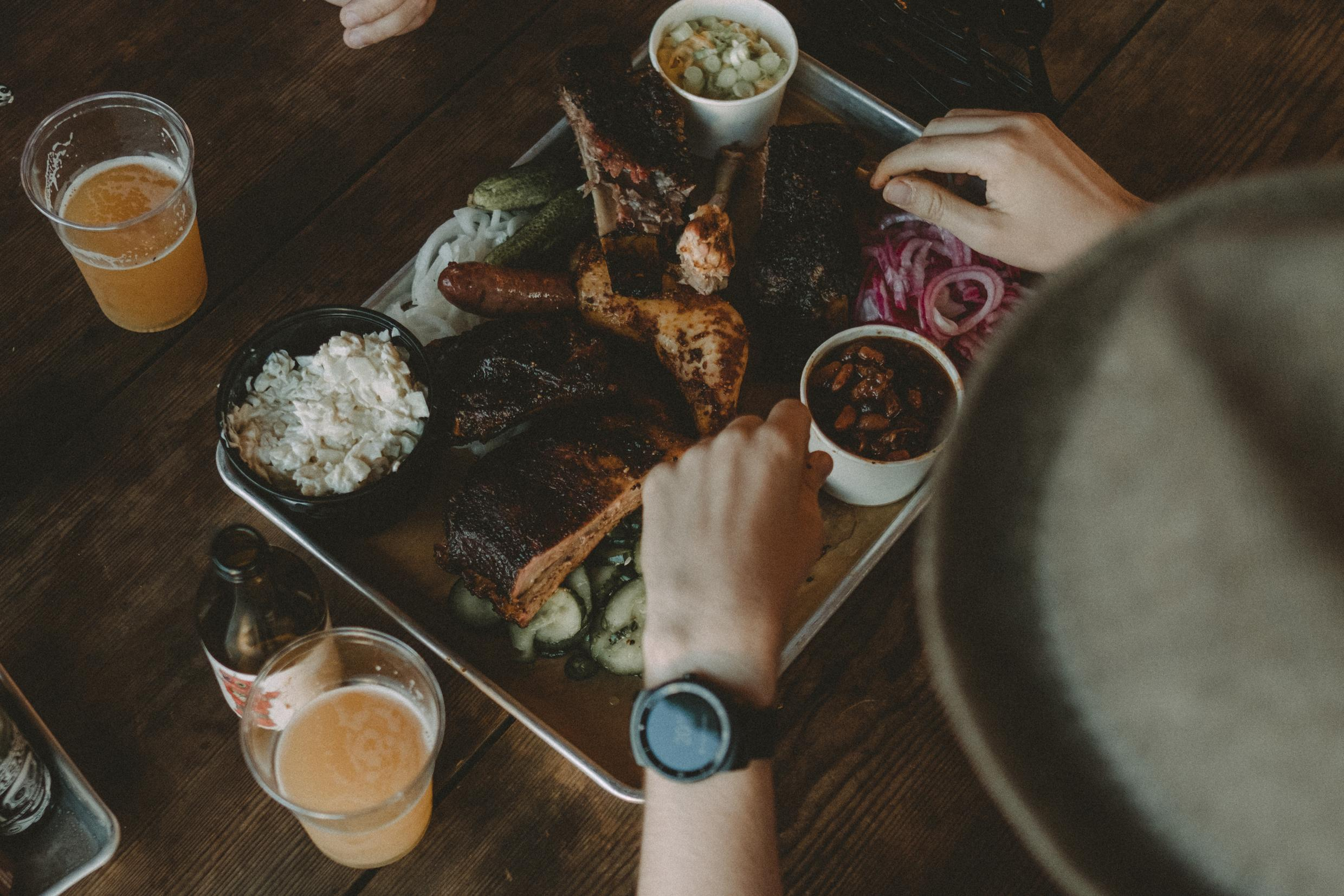 BBQ food on steel plate with beer and person eating