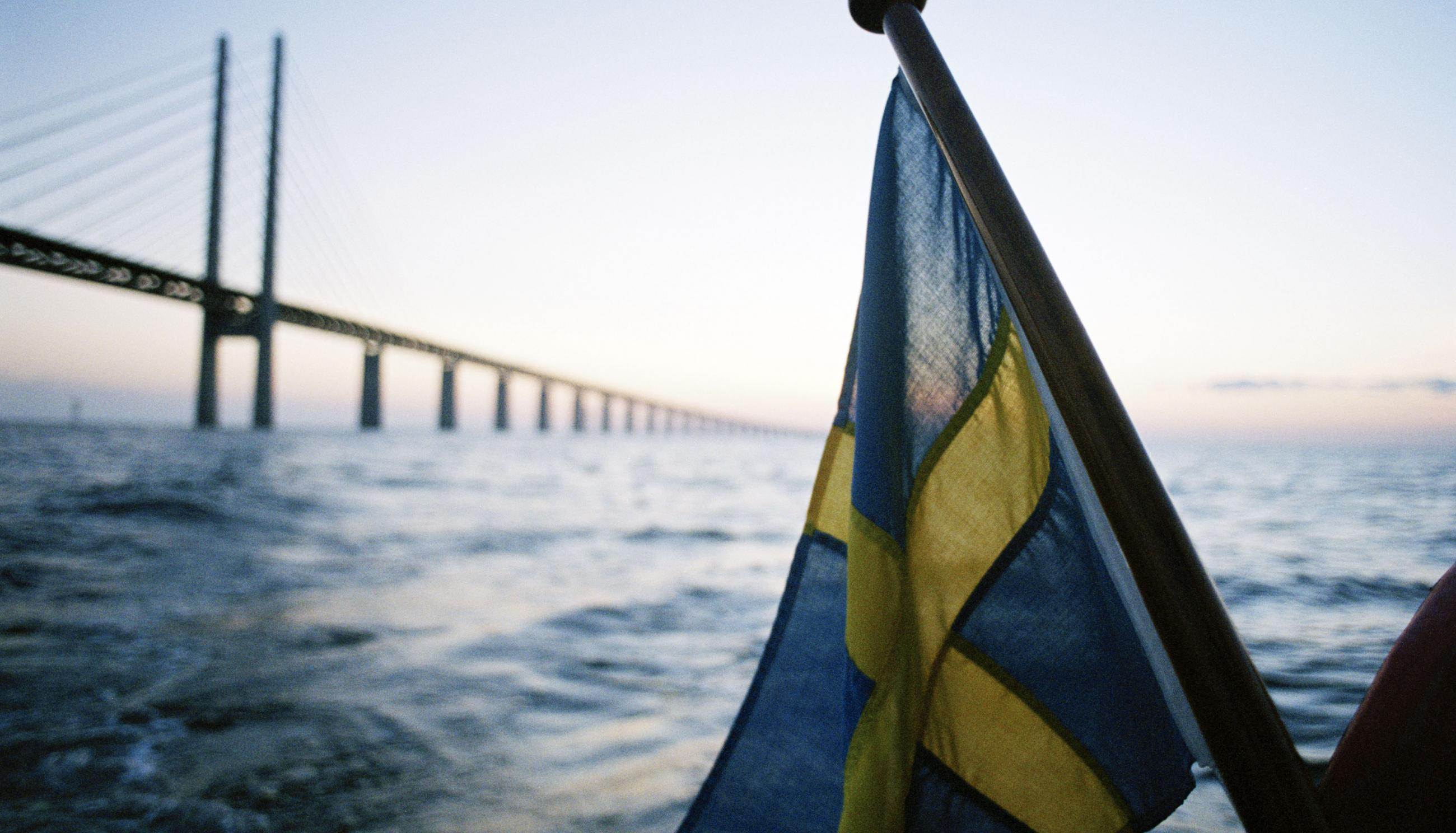 Swedish flag in front of large bridge in the sea