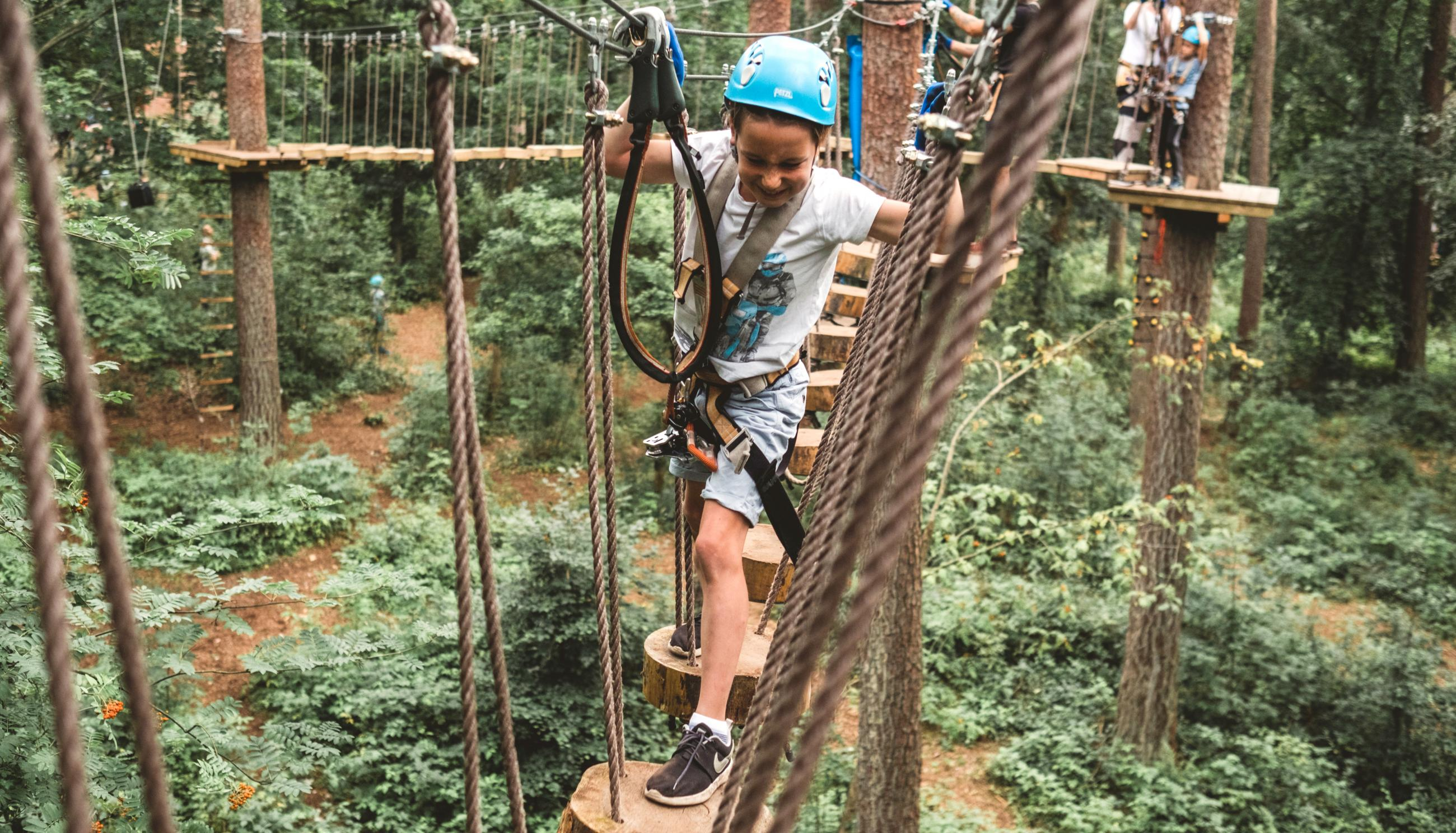 Child with helmet climbing in treetops at upzone