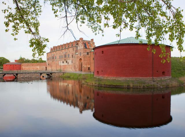 Brick castle with red round side building mirroring in the surrounding water