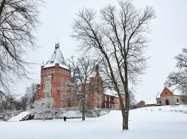 Brick castle in winter with snow on the ground and roof