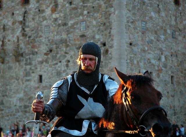 Knight on a horse with blood in his face and a sword in his hand