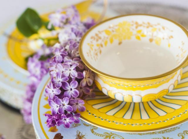 Yellow tea cup with a purple flowe