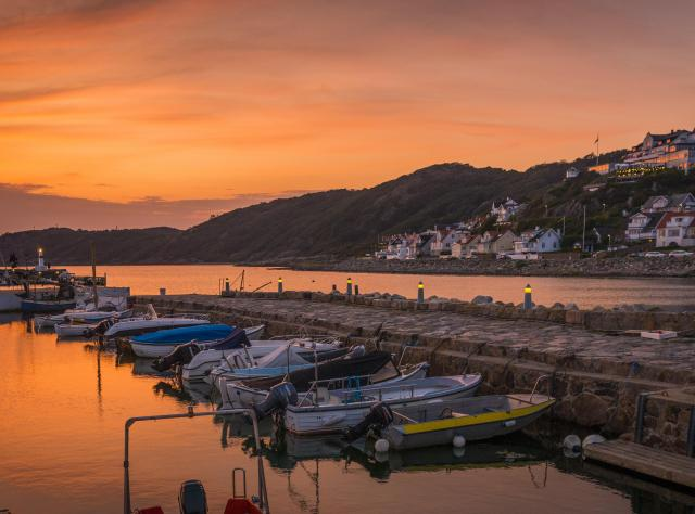 Marina with the picturesque village of Mölle in the background at sunset