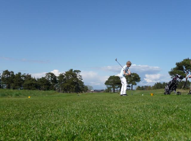 Ground view of golfer swinging bat on a summers day