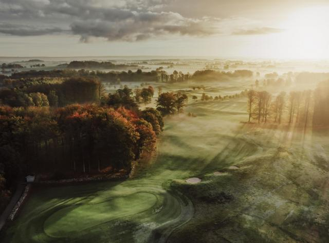 View of golf field with mist and sunshine