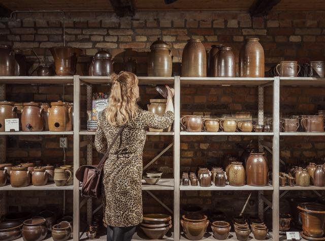 Woman browsing ceramic pots on shelves