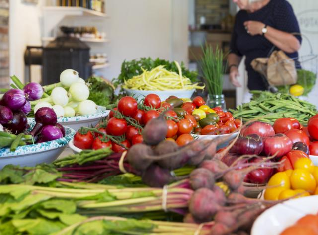A mix of Vegetables on a table and a woman shopping in the background