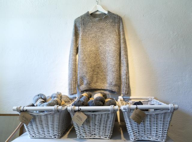 A wool sweater hanging on the wall with three baskets underneath containing yarn.