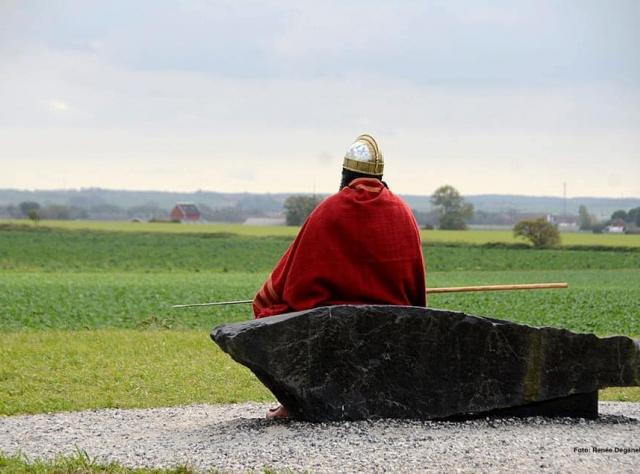 Man sitting on a stone looking out over a field.